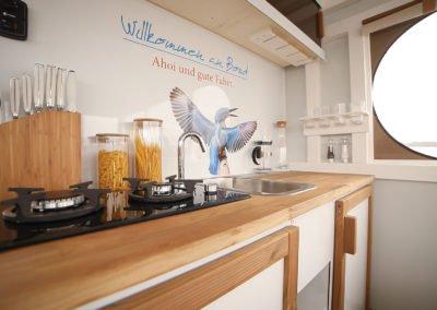 Küchenecke mit Herd und Spüle im Eisvogel Maxi Hausboot