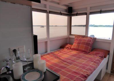 Doppelbett mit Kückenecke im Mini-Hausboot